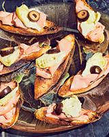 mortadella-artichoke-heart-and-olive-crostini_102801731.jpg