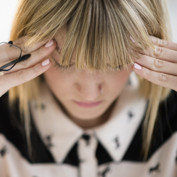 woman headache hands on head