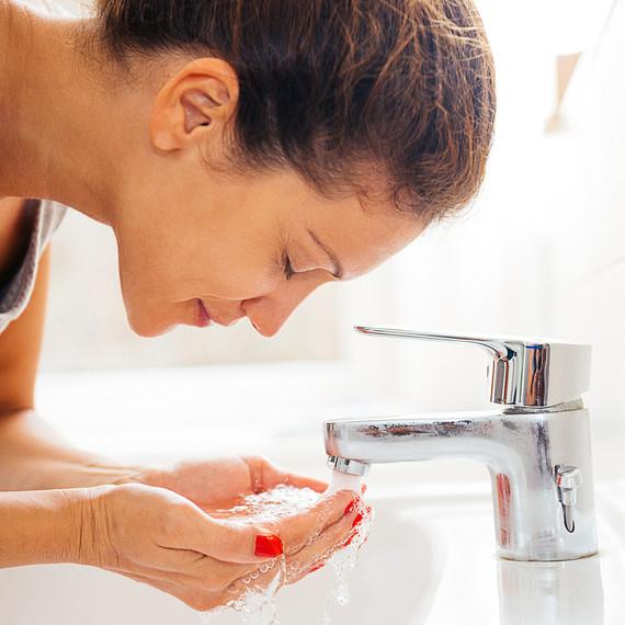 woman rinsing face in bathroom sink