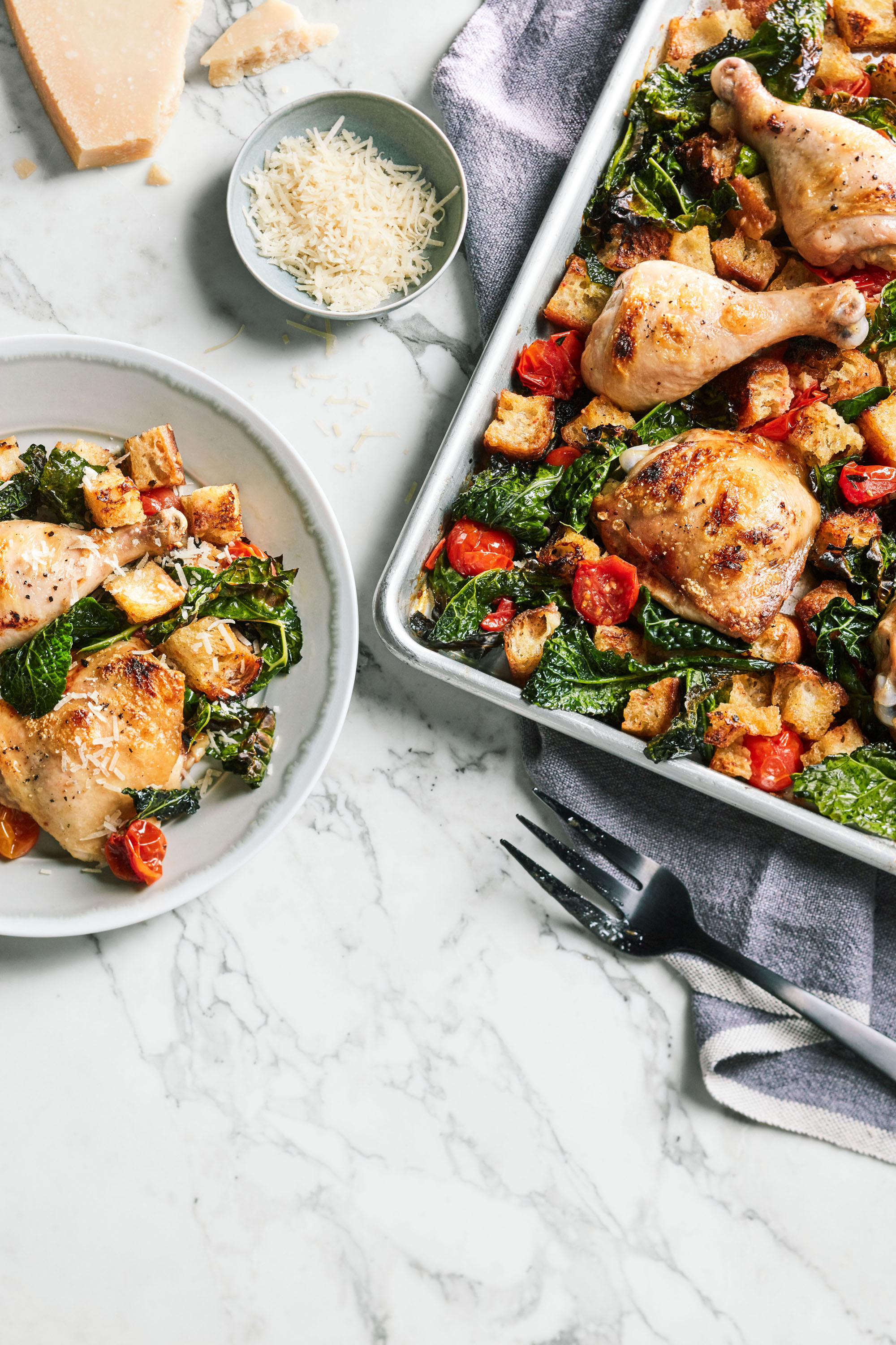plate and sheet of chicken and kale dinner on marble table top