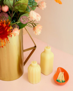 two white bottle candles and vase of flowers