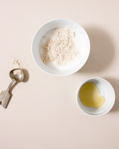 ingredients for oatmeal soap blended in bowls and a silver spoon