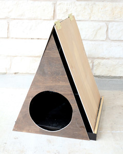 door with circular cutout attached to hinged triangular roof