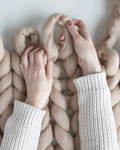 hands forming loops on top row of arm knit blanket