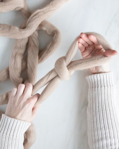 hands pulling slip knot for arm knit blanket