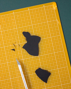 cutting out rabbit outline on black card stock with xacto knife