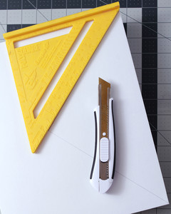 yellow speed square and utility knife atop white rectangular box