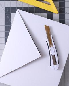 utility knife and cut white rectangular box