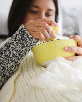 woman squeezing lemon into soup bowl