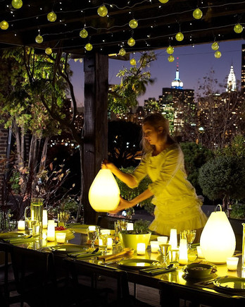 woman setting a table with outdoor party lights overhead