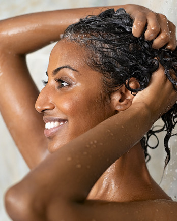 woman smiling while washing hair in shower