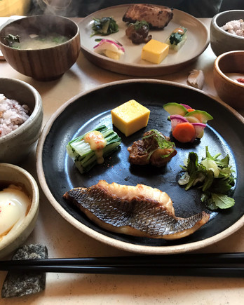 table with plated japanese meals of fish and tofu