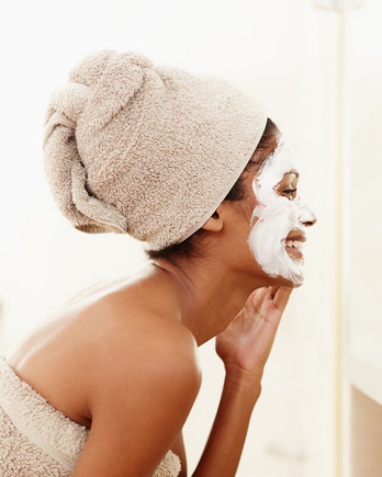 woman putting on face mask at home