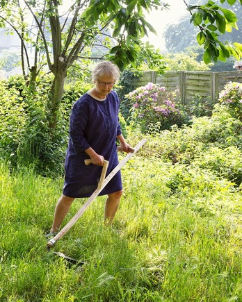 woman scything grass in yard
