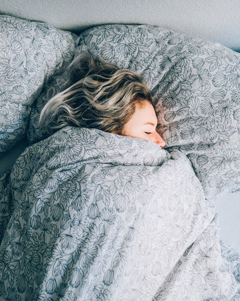 woman sleeping in bed with phone