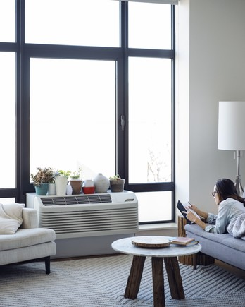 Woman laying down on sofa in living room with air conditioner