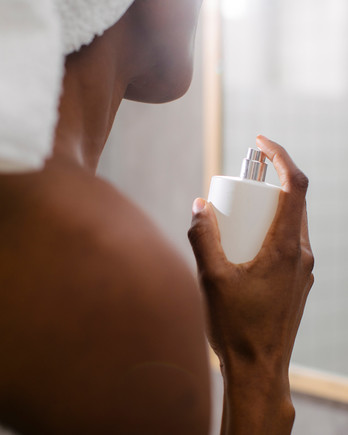woman spraying perfume after shower