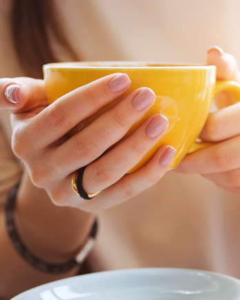 woman with neutral painted nails holding yellow coffee mug