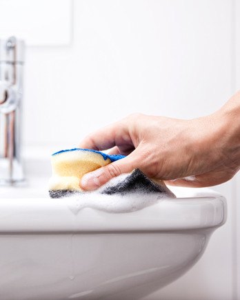 woman cleaning sink with sponge