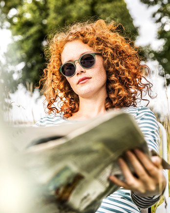 woman with curly red hair reading newspaper