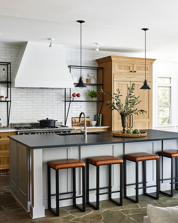 large, open kitchen with white walls, black counter top and light wood