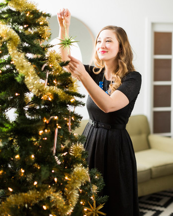 woman hanging star ornament on christmas tree