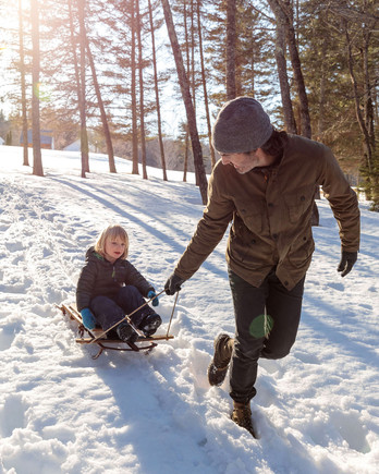 man pulls child on wooden sled across snow