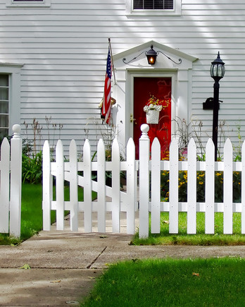 white picket fence around white house with red front door