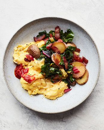 bacon potato and swiss chard scramble served on grey plate