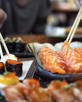 people eating a salmon fish sashimi and sushi in Japanese restaurant