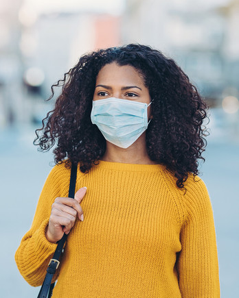 young woman walking outdoors with a face mask