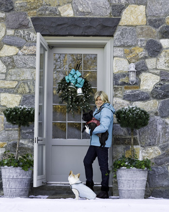 Martha Stewart standing at the front door during Christmas