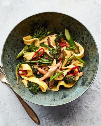 egg noodle broccolini and mushroom stir fry served in green bowl