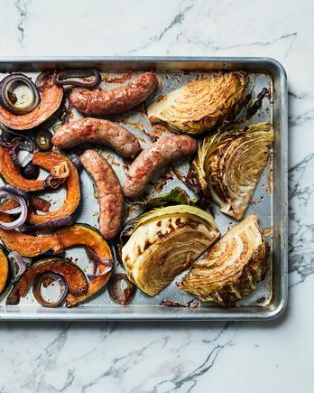 sausages cabbage vegetables on baking sheet