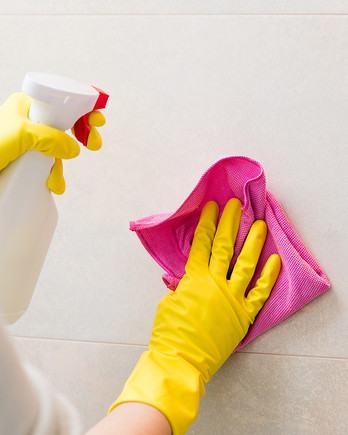 woman in yellow gloves cleaning bathroom tile