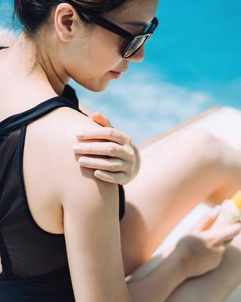 woman applying sunscreen to shoulder