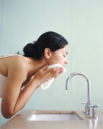 woman washing face with white wash cloth