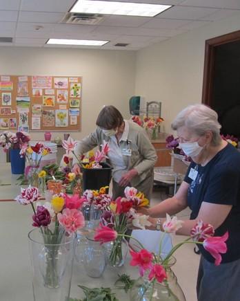 Women arranging tulips at senior center
