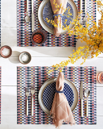 colorful tablescape with multiple patterns and yellow flowers and lemons