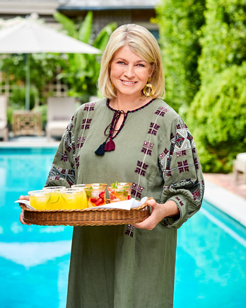 Martha Stewart standing by pool holding cocktail tray