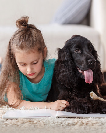 girl lying on floor reading book with dog