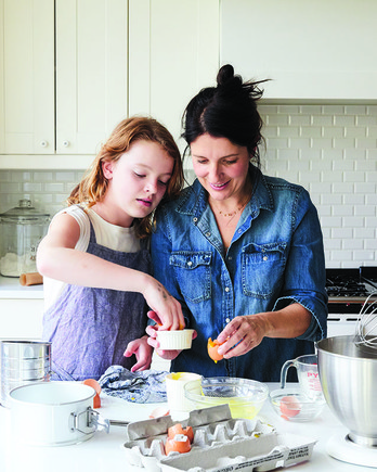 mother and daughter baking cake in neutral colored kitchen