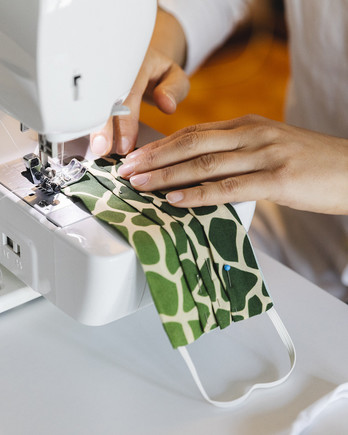 woman sewing green protective face mask on sewing machine