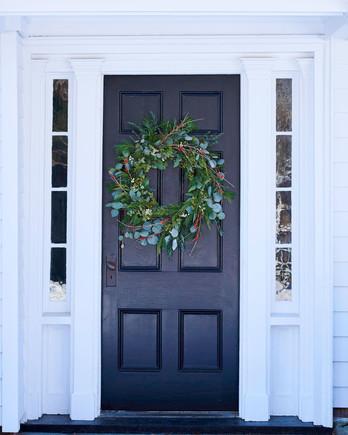 winter wreath on front door of white house