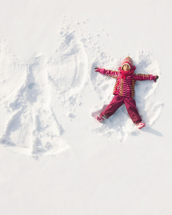child in pink coat making snow angel