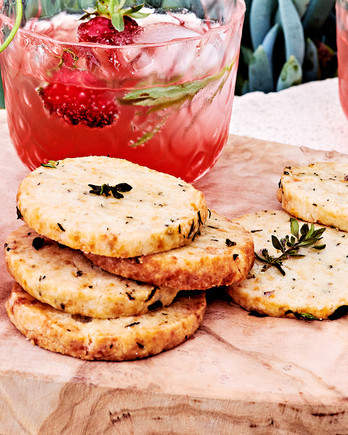thyme-scented parmesan-almond crackers served on wooden cutting board