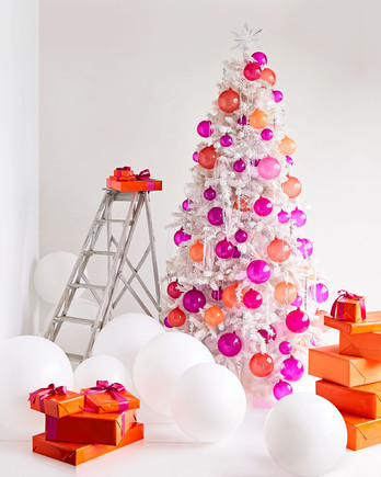 white christmas tree decorated with orange and pink handblown glass balls