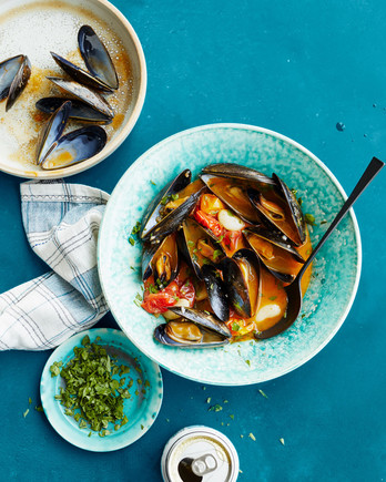 drunken mussels with chorizo and white beans topped with parsley leaves