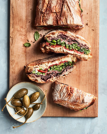 pressed sandwich with prosciutto and broccoli rabe recipe on wooden cutting board