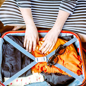Woman in striped dress packing a suitcase
